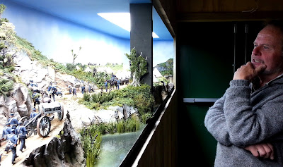 Man standing thinking in front of a diorama of 19th-century soldiers in the bush.