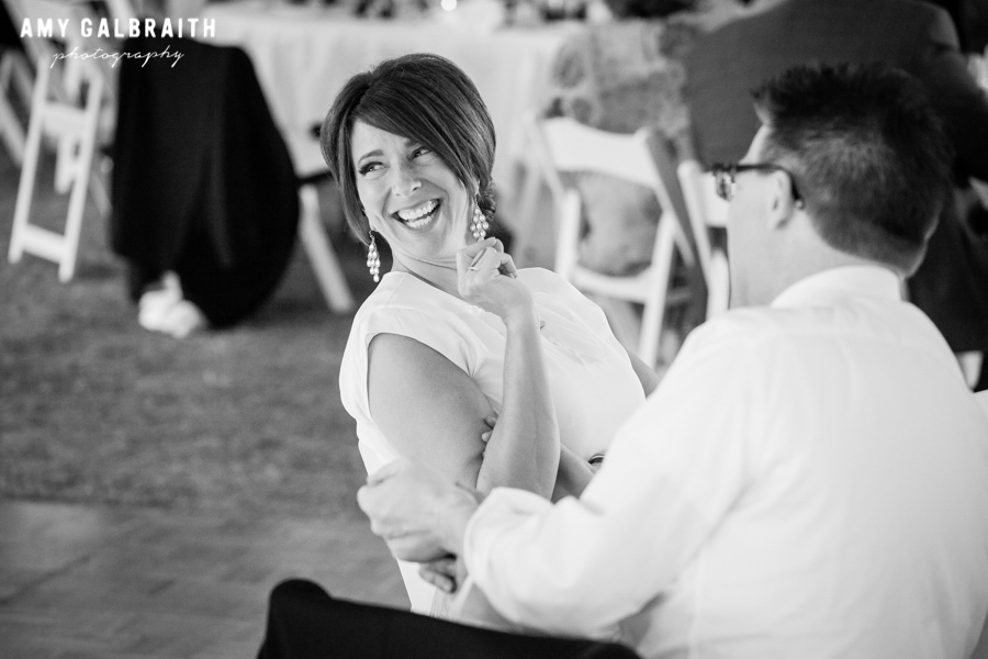 black and white image of woman laughing at wedding reception