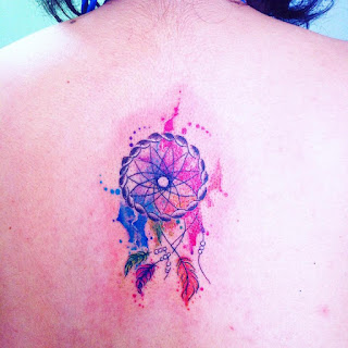 Tatuaje de atrapa sueño en la espalda estilo acuarela