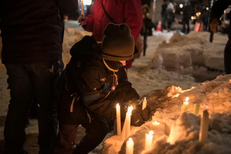 A boy lights a candle at a mass memorial to victims of a shooting at a mosque in Quebec City, Canada on January 30, 2017. A Canadian student known to have nationalist sympathies has been charged with six counts of murder over the January 29 attack
