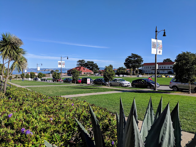 Alcatraz is visible in the Bay from the steps of the Disney Family Museum. The grassy Parade Ground is bordered by sidewalks and flower beds.