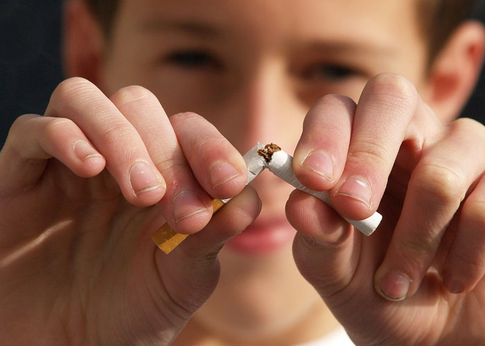 menino quebrando o cigarro no meio