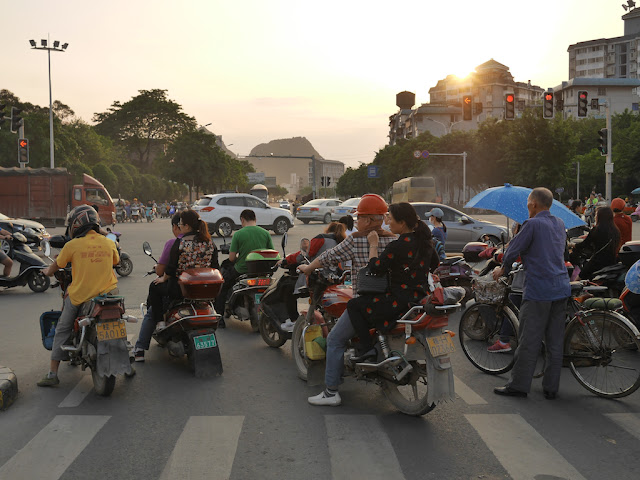 people on motorbikes and bicycles waiting for the light to change at an intersection in Guilin