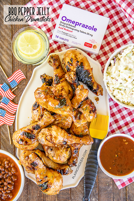 grilled chicken drumsticks with baked beans and slaw on a table
