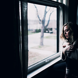 Young girl standing looking out of a window
