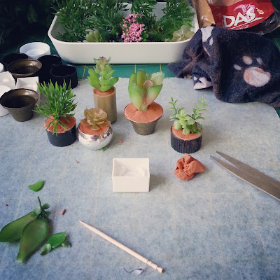 Five one-twelfth scale potted plants on a cutting mat surrounded by empty pots, spare foliage, a pack of air-drying clay and a cleaning rag.
