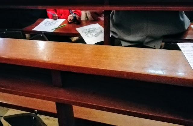 Kerkbank waar tussendoor je twee meisjes een kleurplaat ziet kleuren op de bank ervoor.