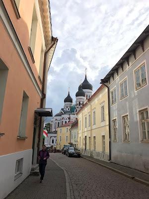 Smal gate mellom murbygninger i lyse farger. I bakgrunnen sees noen kirketårn med løkkupler.