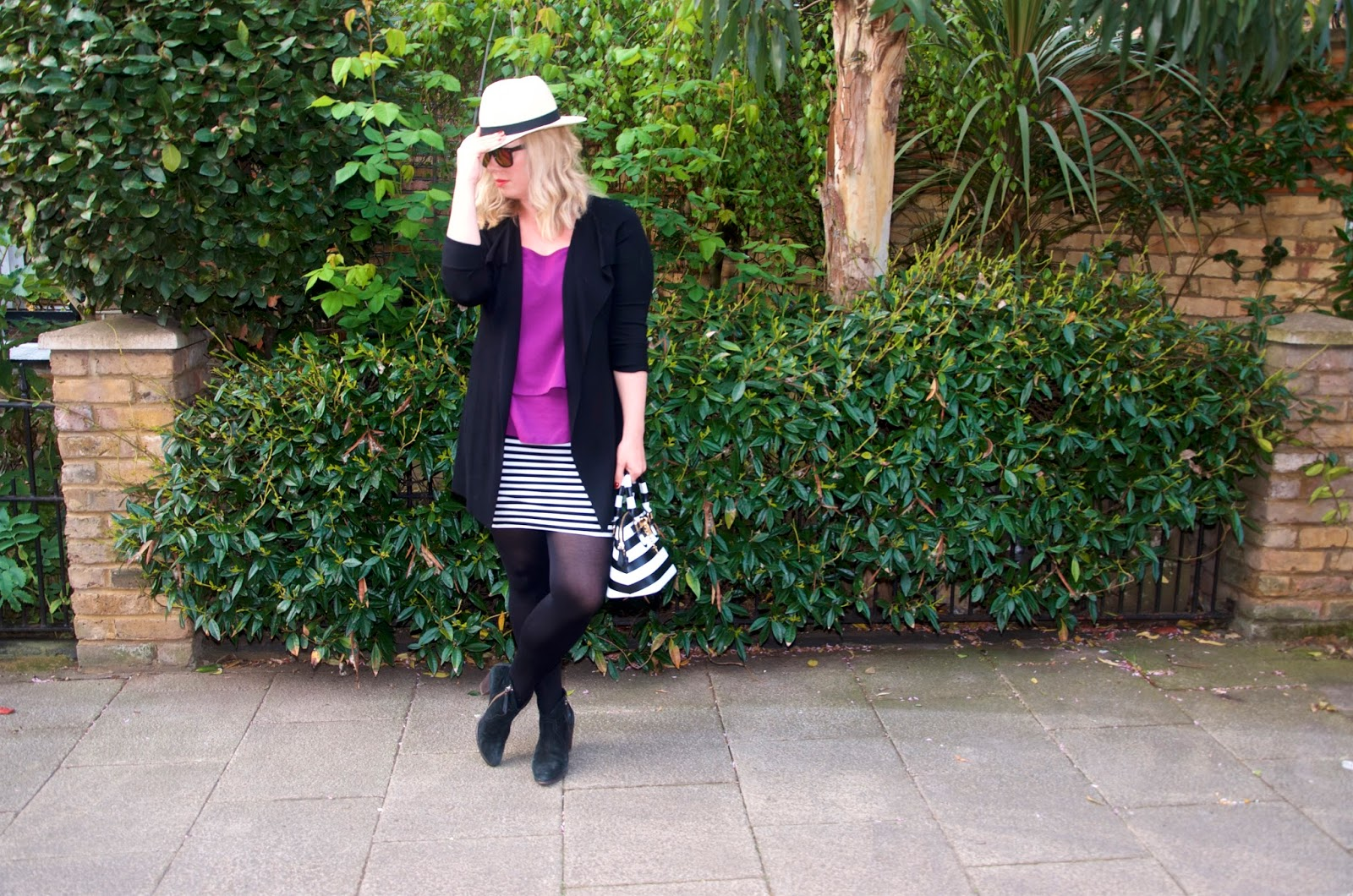 Fuchsia top, striped skirt, striped bag, fedora, tights, suede boots, black cardigan, mirror sunglasses