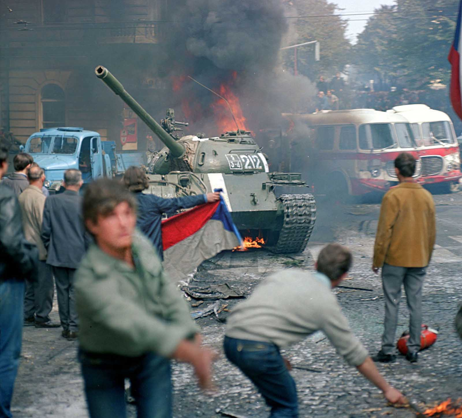 Prague residents, carrying a Czechoslovakian flag and throwing Molotov cocktails, attempt to stop a Soviet tank in downtown Prague on August 21, 1968.