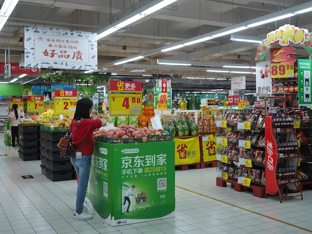 woman choosing apples at a Carrefour in Zhongshan, China
