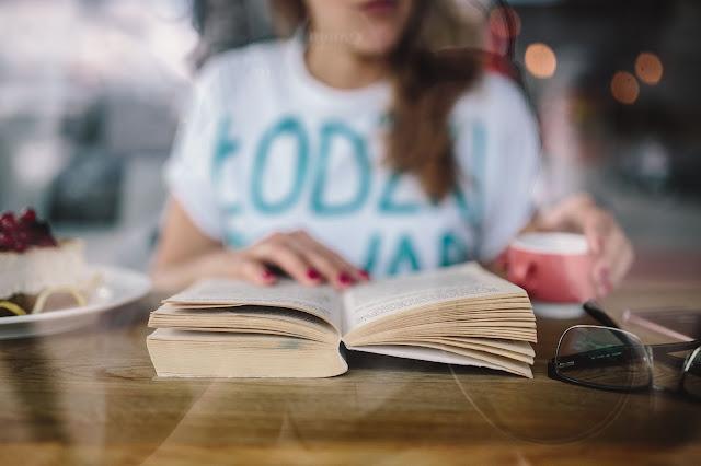 Uma mulher jovem a ler num café