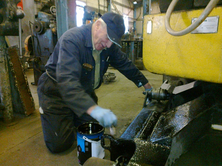 In the workshop, Ron paints the New Holland excavator