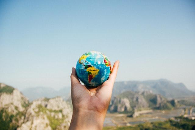 Mano sujetando una pequeña bola del mundo