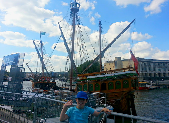 Boy standing in front of The Matthew at Bristol Harbour
