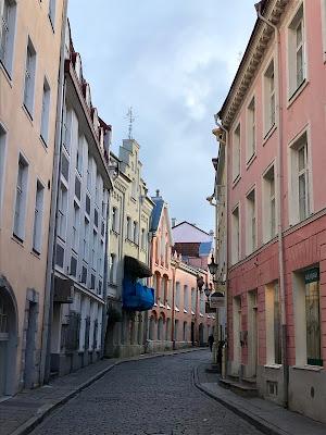 Kurvet gate mellom pastellfargede hus.