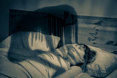 sombra aterrorizando a joven mujer en parálisis de sueño