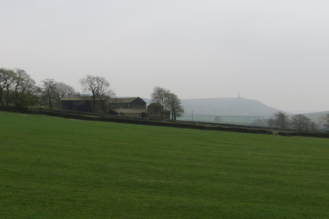 A view back across an open field, farm buildings to the left and in the distance Stoodley Pike monument on the hilltop.