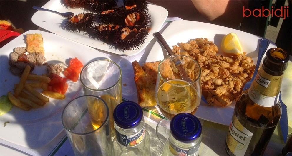 table de restaurant au soleil avec tapas oursins et biere à Calella Costa Brava Espagne