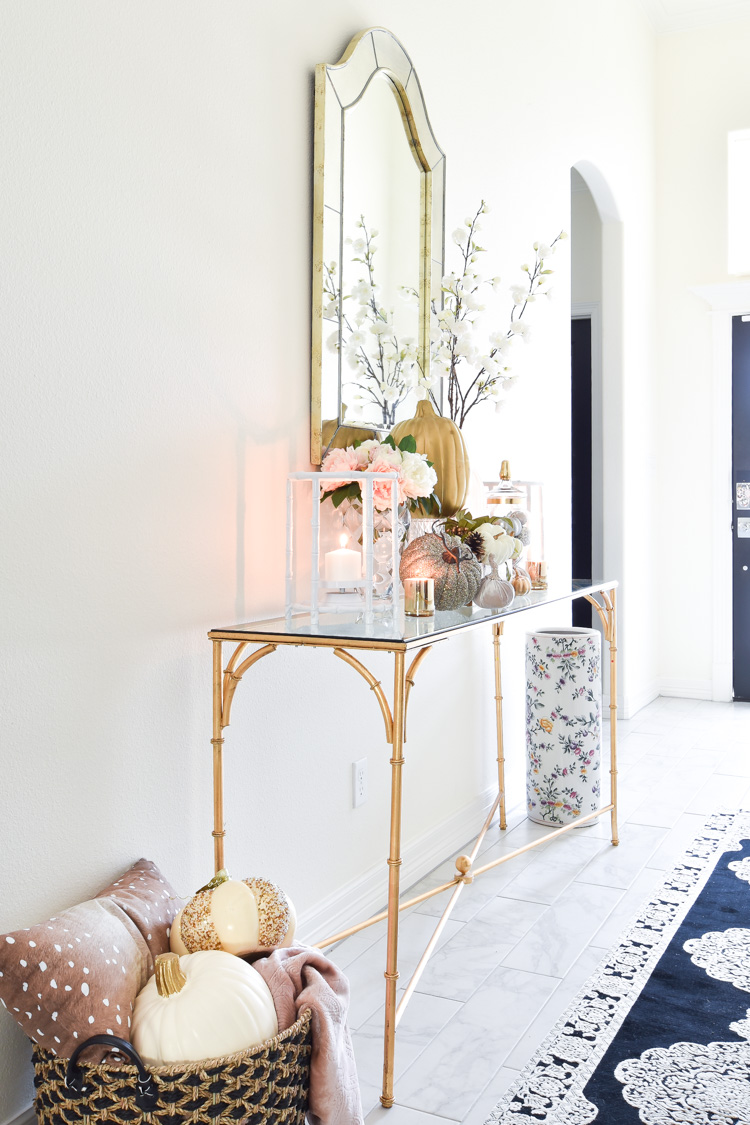 A white foyer goes glam with gold, pink and silver fall decor accents on a bamboo console table.