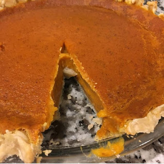 pumpkin pie with one slice taken out of it