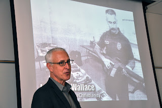 J. Warner Wallace stands next to a picture of himself as a SWAT officer.