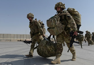 blog picture of soldiers carrying a bag between them along with their back packs