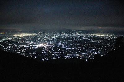 pemandangan lampu kota dari jalur pendakian ke puncak