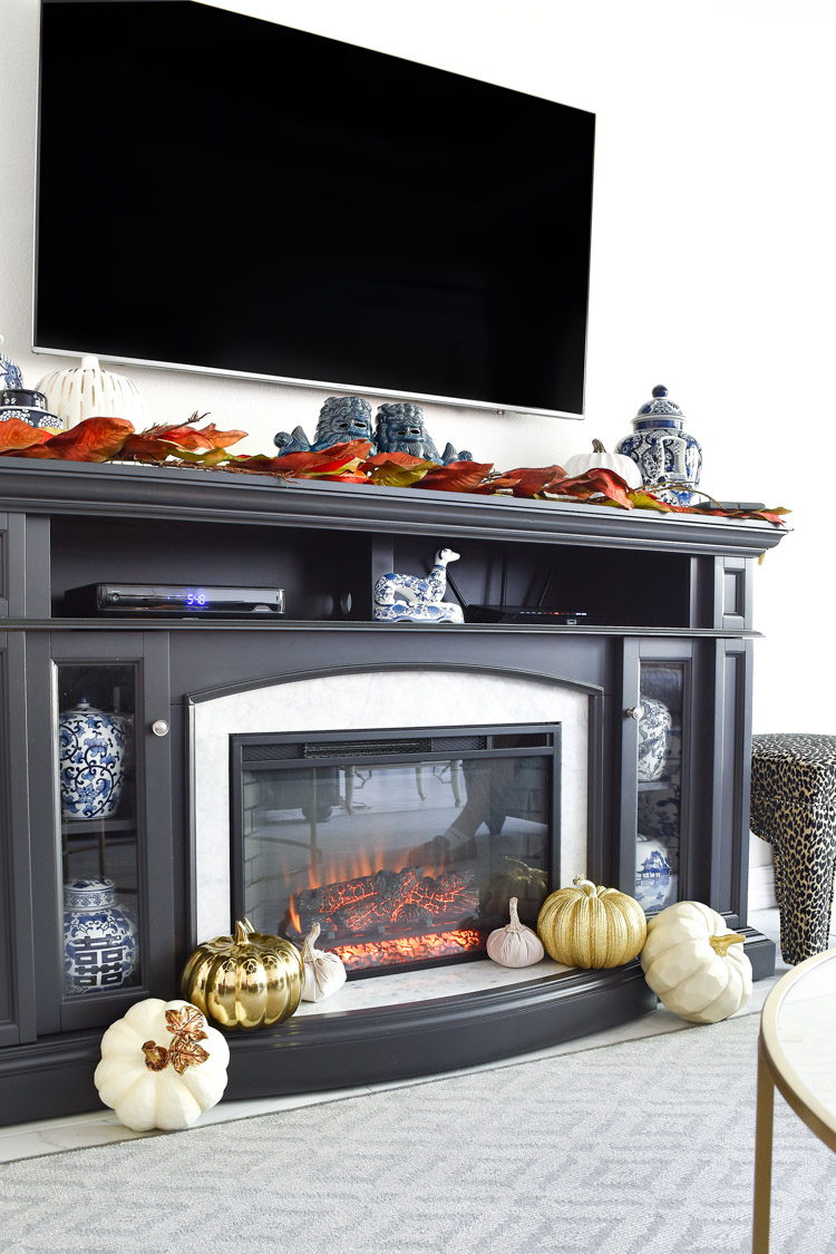 Foo dogs, ginger jars and other blue and white chinoiserie decor paired with white and gold pumpkins on a gray marble fireplace TV stand.