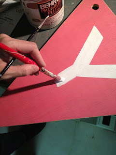 handpainting letters onto wood bunting