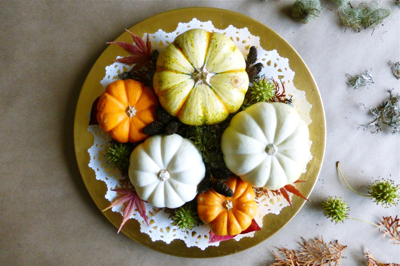 mini pumpkins, gold charger plate, doily, arborvitae sprigs, sweet gum seed pods, blueberry leaves, Japanese maple leaves, moss, alder seed cones