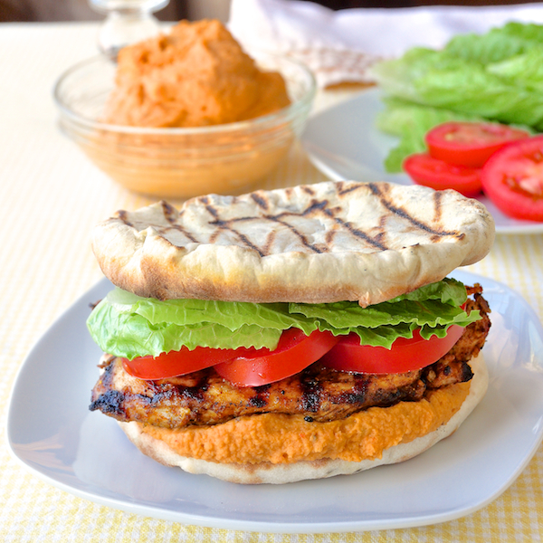 Moroccan Marinated Grilled Chicken Flatbread Burgers with Red Pepper Hummus - a simple, spiced marinade flavors the chicken while the flatbreads are made on the grill right alongside it. Creamy red pepper hummus completes this delicious combination of flavors and textures.