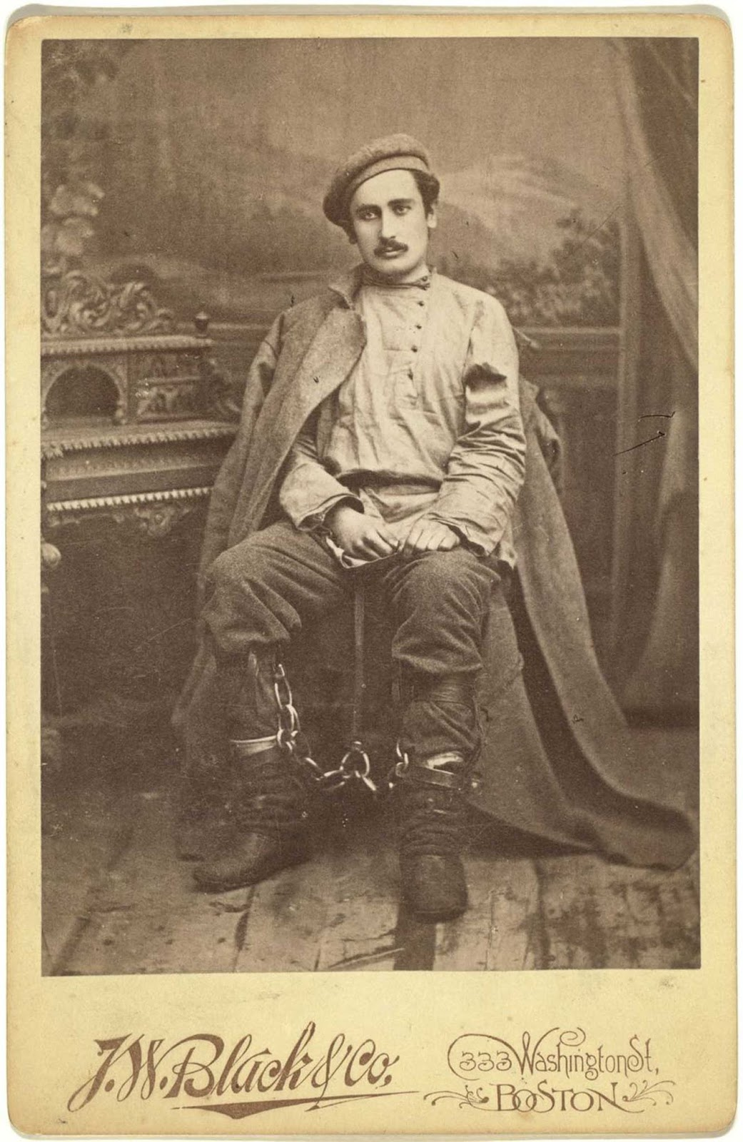 A studio portrait of a Russian prisoner in leg irons.