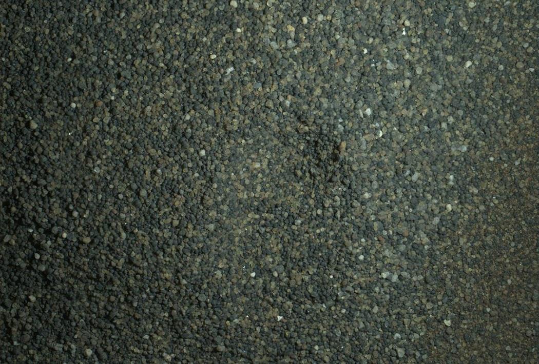 Thiết bị chụp ảnh Mars Hand Lens Imager được gắn ở cánh tay robot của tàu Curiosity sử dụng đèn pin để chiếu sáng mặt đất vào ban đêm, cho thấy những hạt cát trên bề mặt Sao Hỏa được tàu tự hành sàng lọc và phân tích. Kích thước của hình ảnh này trong thực địa chỉ 2,8 cm chiều dài và 2,1 cm chiều rộng. Các hạt cát này quá lớn để lọt vào lưới của tấm sàng (150 micron so với 0,006 inch). Chúng là muỗng cát đầu tiên mà tàu Curiosity múc lên từ Đồi cát Namib. Một phần nhỏ của số cát này đủ nhỏ để sàng lọc và đưa vào thiết bị phân tích được trang bị sẵn trong tàu. Hình ảnh này được ghép lại từ nhiều ảnh đơn để làm rõ các chi tiết, được chụp vào ngày 22 tháng 1 năm 2016, sau khi màn đêm vừa buông xuống của sol 1230. Hình ảnh: JPL-Caltech/MSSS/NASA.