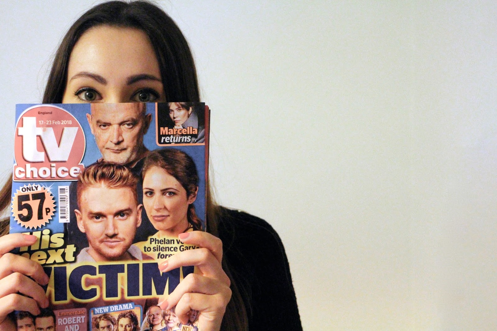 Blogger with a TV guide on front of face