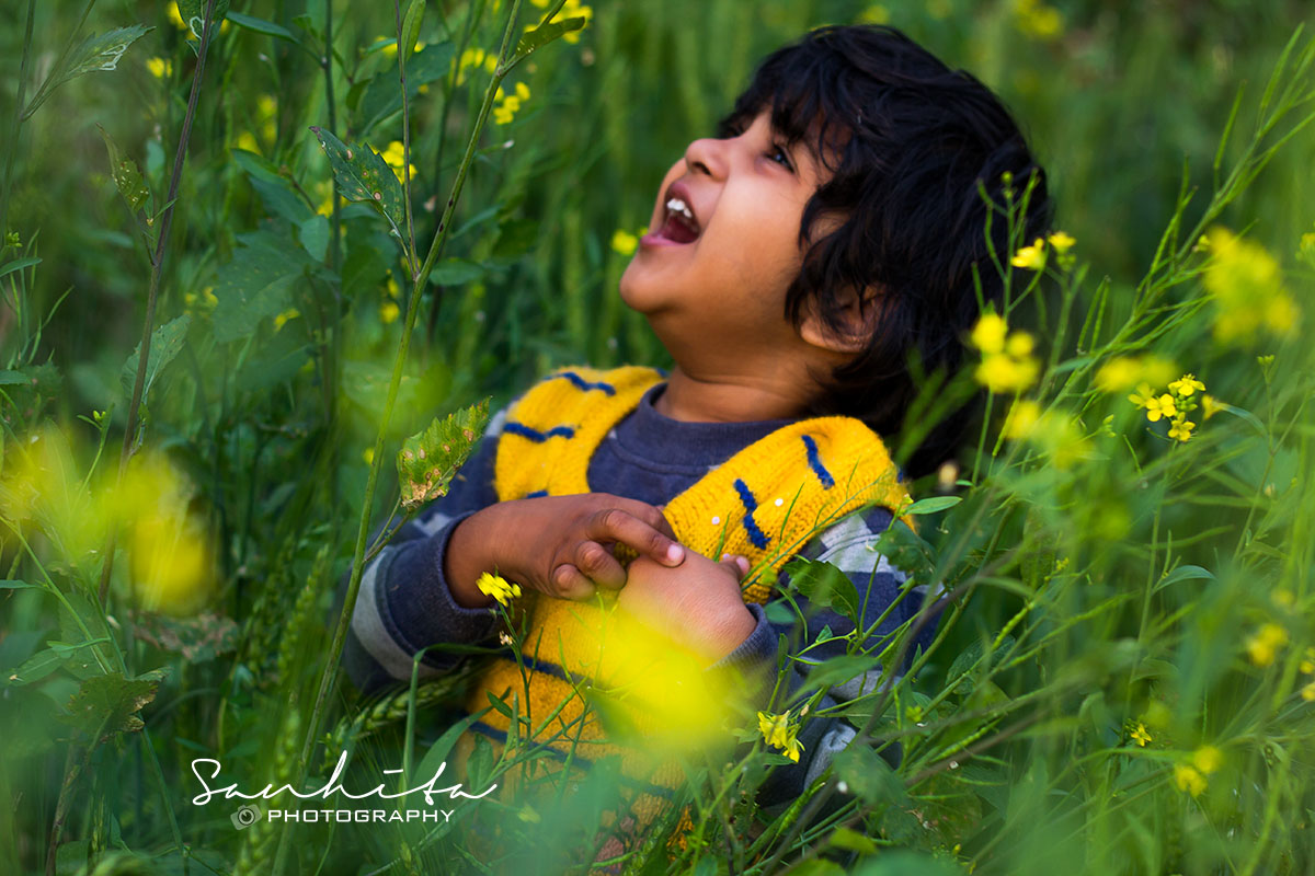 A happy kid enjoying herself among tall grasses