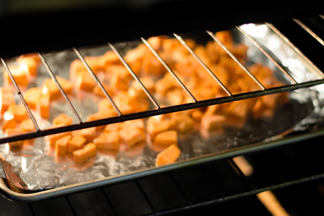 The seasoned sweet potatoes on the baking sheet into the oven.