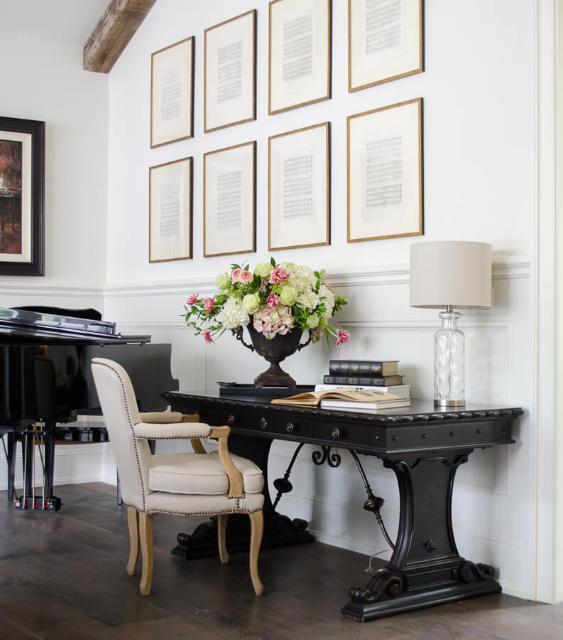 living room with framed vintage sheet music and desk