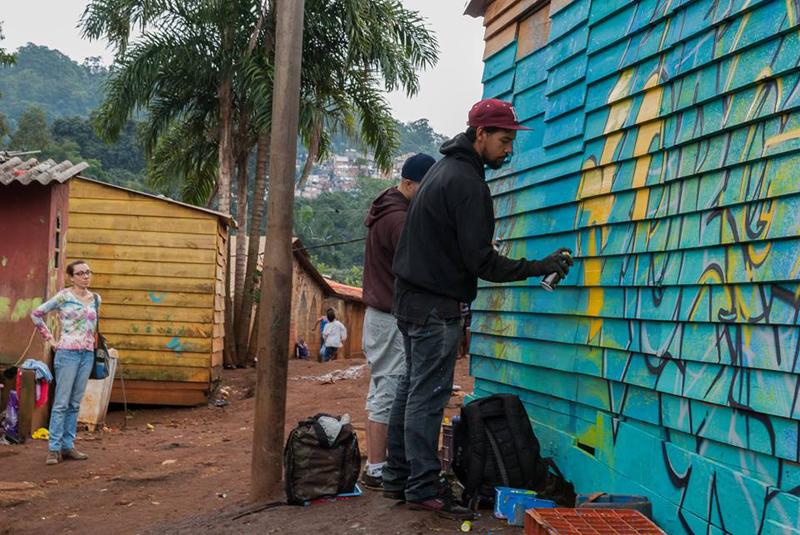 A bióloga Natasha Ceretti que estava pesquisando o TI Jaraguá observa o início da produção de um dos painéis de grafite. Foto: Nelson Luiz Batista