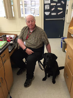 William and Guide dog Leif sit at a desk waiting for the next class of middle school students to arrive for the presentation on living with blindness and working with a guide dog.