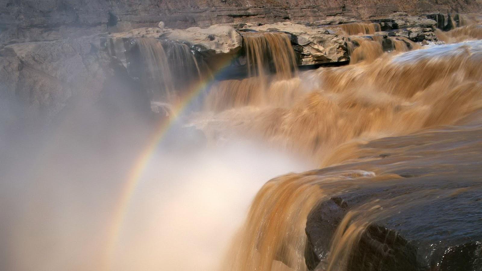 Bruin water, waterval en een regenboog
