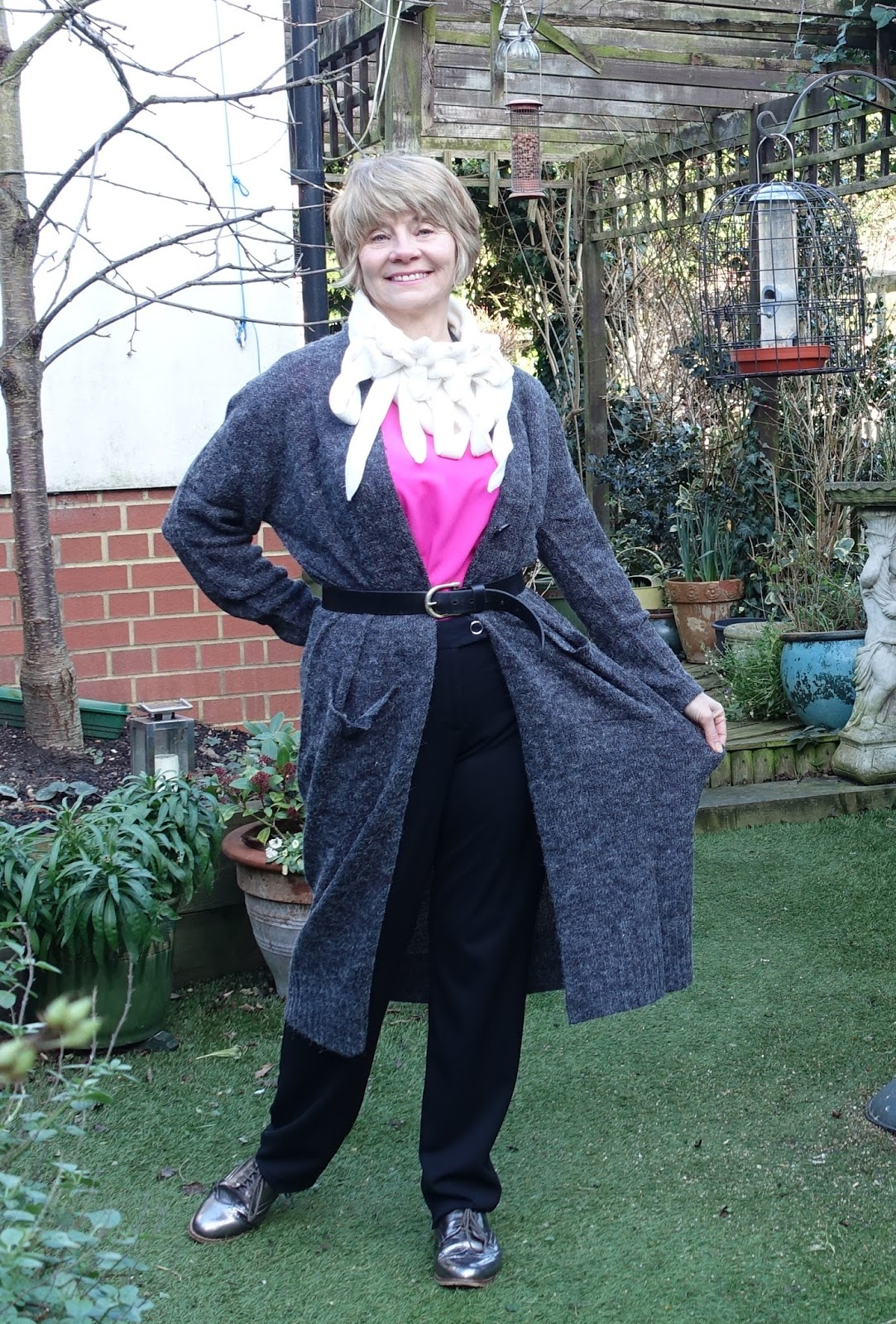 Image showing a fashion conscious middle aged woman wearing a long line knitted grey cardigan worn over black trousers and metallic brogues, with a pink top and cream fleecy neck wear.