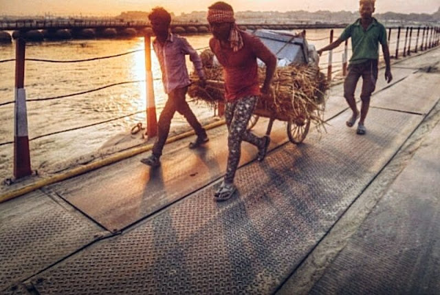 Workers carry goods to build huts on the banks of the Ganges river ahead of Kumbh Mela