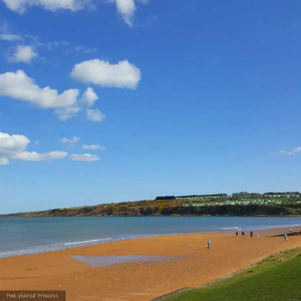 beautiful bright sunny day with blue sky sandy beach and the Scottish coastline