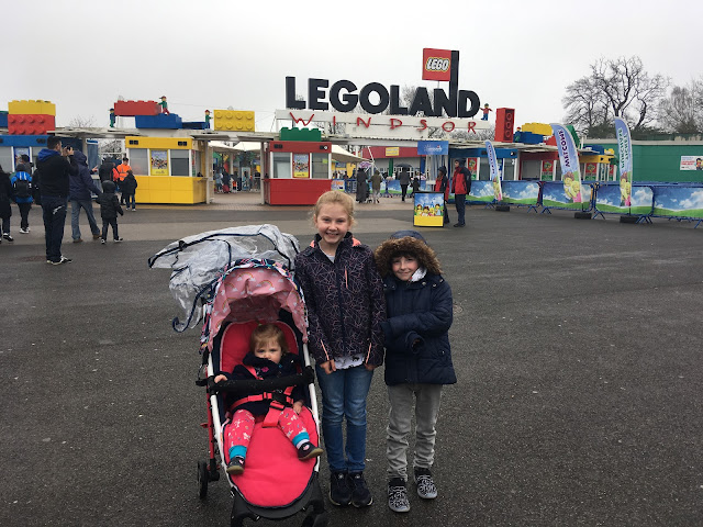 three children, one in a pushchair at the entrance to legoland windsor
