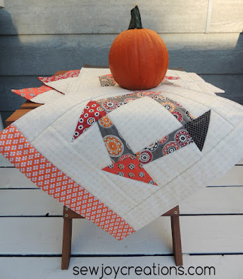 Liberated Churn Dash placemats posing with a pumpkin