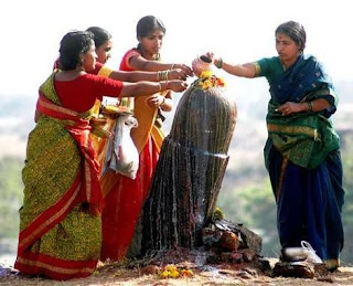 Indian women pouring milk on phallic idol shivalinga as worship of Lord Shiva