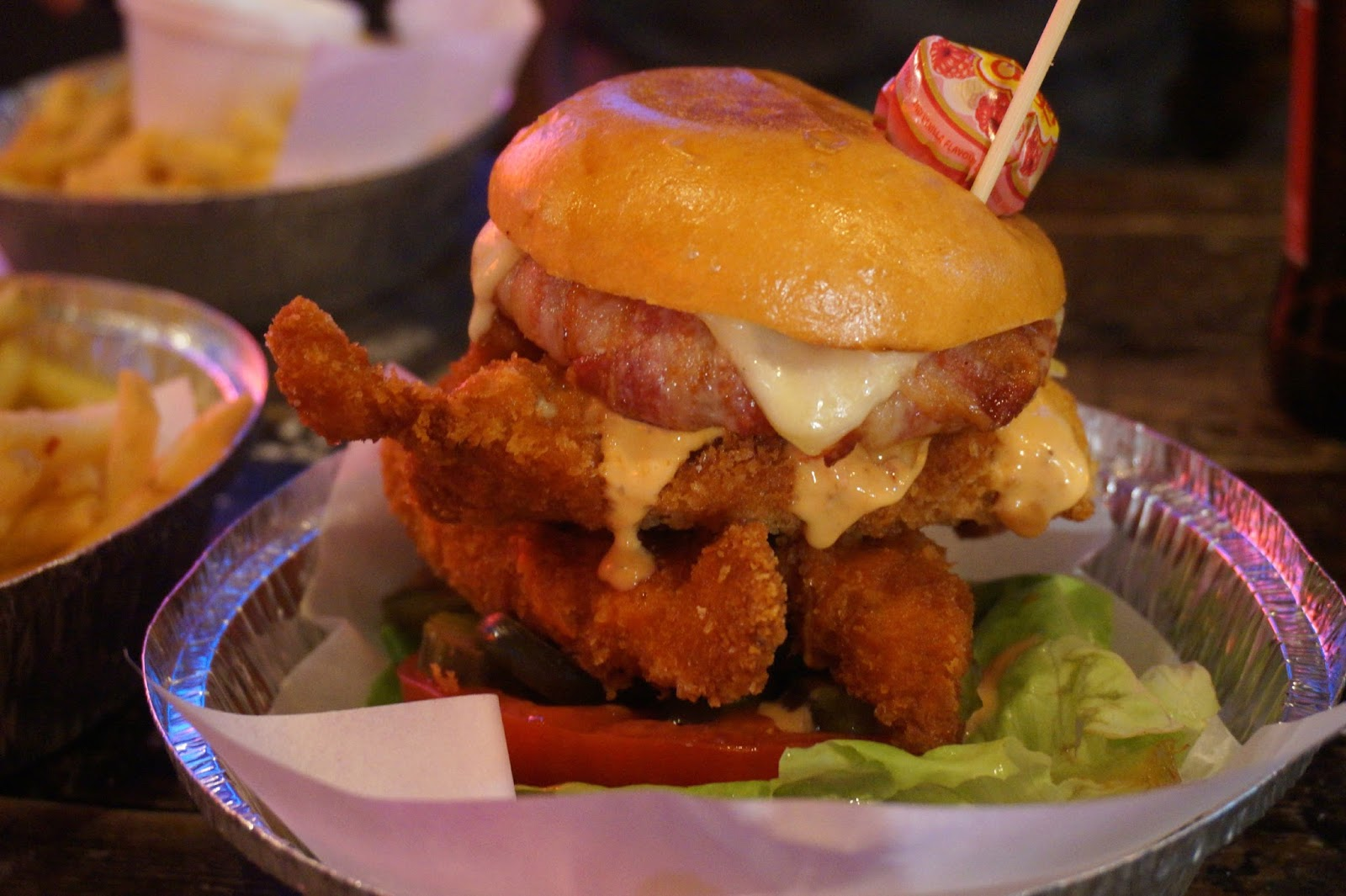 double chicken burger with bacon, swiss cheese, an onion ring and salad
