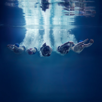 5 swimmers dive into the water at the same time