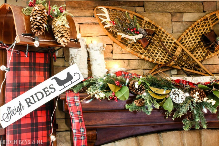 Holiday mantel with birch logs used as candle holders with plaid scarf